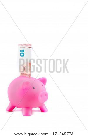 Piggybank with ten Euro banknote and copy space