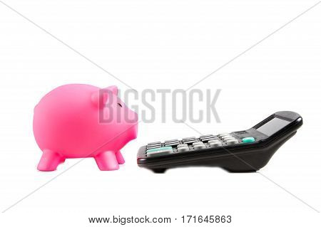 Piggybank and calculator isolated on white background