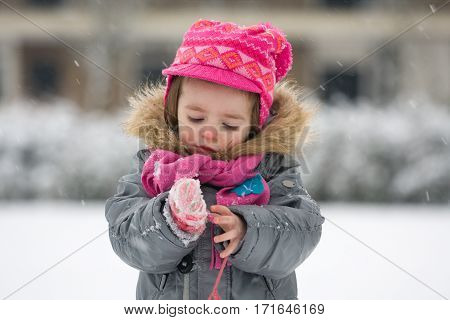 Portrait of young child (infant) outside in snowy weather dressed in winter coat scarf and cap. The girl is watching snowflakes falling on her gloves