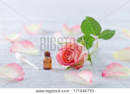 one ml bottle with essential oil, natural rose blossom and pipette on the vintage wooden background