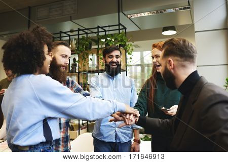 Cheerful male and female team members motivating on informal meeting high-fiving with skilled leader motivate employee working hard and finding creative solution communicating in friendly atmosphere