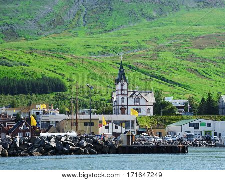The part of the town Husavik in the north-west Iceland with in the main point a white wooden church and port in the background green