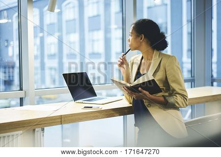 Young attractive female afro american chief economist in company planning formal meeting with partners using laptop computer with blank screen connected to wifi standing on copy space for advertising