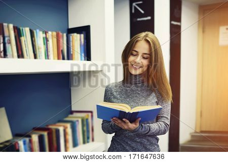 Young charming cheerful female librarian looking for manual book about poetry reading content while standing on background with bookshelves in modern designed interior university library for students