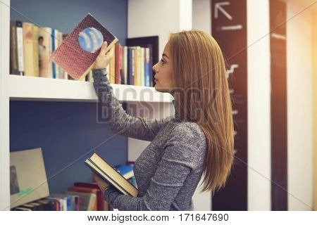Experienced professional attractive female librarian putting in alphabetical order book on shelves returned from readers working in modern designed interior university library for students and pupils