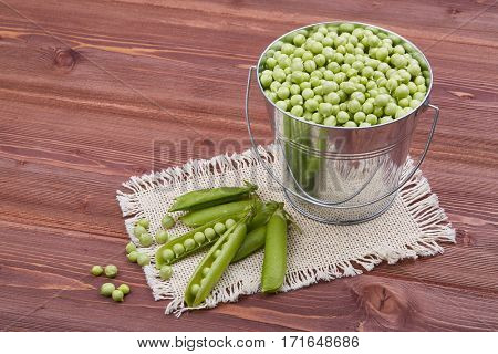 Bucket with fresh green peas and  ripe pea pods on a wooden table. Harvesting.