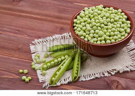 Bowl with fresh green peas and  ripe pea pods on a wooden table.
