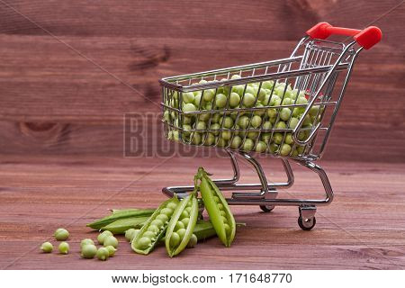 Shopping trolley with fresh green peas and  ripe pea pods on a wooden table.