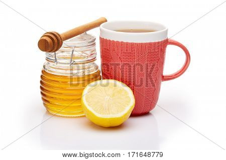 Honey in glass pot and mug of tea with lemon on a white background.