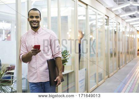 Portrait of cheerful male student watching funny videos in social network while chatting with best friends during lesson break using wireless connection to internet in university free wifi zone