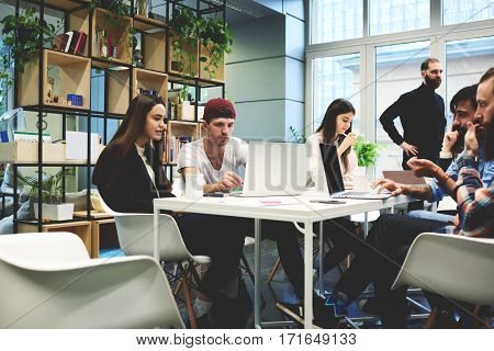 Skilled woman with her male colleague sitting at laptop computer in large office. Group of students information technology education preparing coursework about development of programs and applications