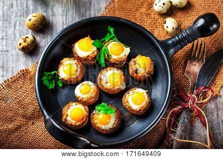 Mushrooms with quail eggs. Mushrooms on black pan. Quail eggs and cutlery close. Selective focus