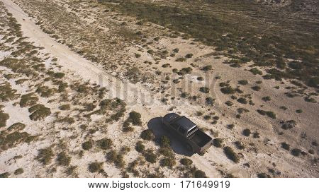 Aerial photo from flying drone of a riding pickup car in Texas desert with arid climate and dry landscape. Tourists having leisure time with rental automobile during their road trip to America