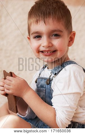 Little Boy With A Big Bar Of Chocolate In His Hands