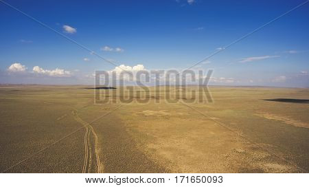 Top view aerial photo from drone of off road way with tires of car in arid dessert valley landscape. Beautiful nature view with copy space area. Concept of freedom of choice of destination in travel