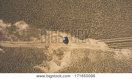 Top view aerial photo from drone of a riding pickup machine in sandy steppe during amazing trip to Asia. Professional rider is drifting in desert arid wilderness leaving circle trails of the tires