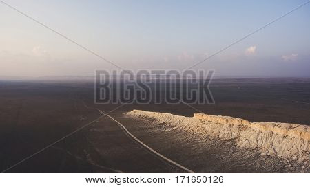 Aerial photo from airplane cockpit of dessert valley with reflected sunset light on horizon.Long sandstone canyon in boundless National Park of America. Nature landscape background for travel website