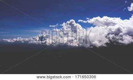 Aerial photo from flying drone of a beautiful cloudy sky over green island. Puffy white clouds with sunlight. Natural skies composition. View from airplane window