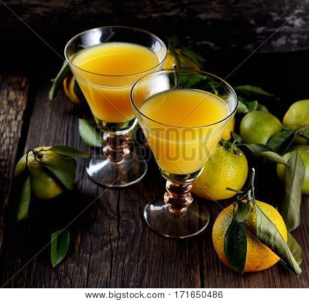 Two Glasses  of fresh tangerine juice with ripe tangerines, leaves and old-fashioned straw on a wooden background