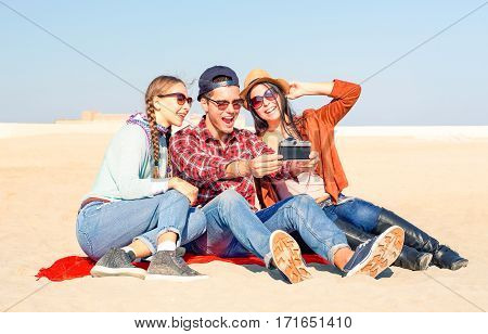 Group of friends taking selfie using old camera sitting on the beach in sunny spring  break day - Cheerful students having fun moments with self photo relaxing on sand - Concept of people leisure at weekend