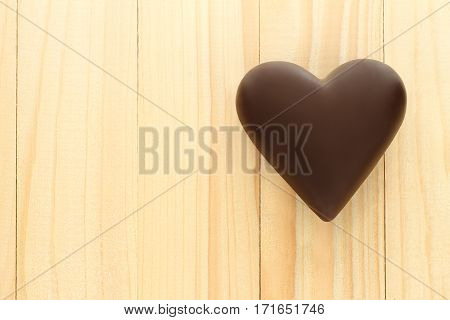 Black chocolate hearts on wooden background close-up