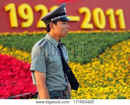 Beijing - July 3: A Soldier Stands Guard Against The Backdrop Of The Communist Symbols At The Tianan