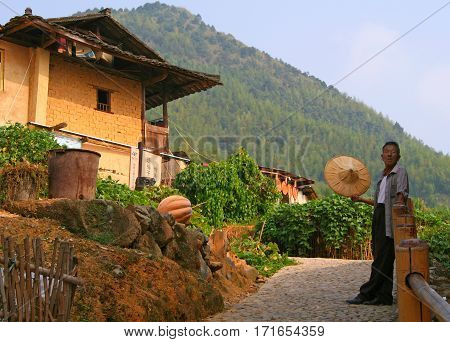 Yongding, China - Oct 21, 2009: Elderly Man, Typical Representative Of The Ethnic Hakka, Near His Ho