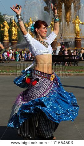 Moscow, Russia - May 18, 2014: Beautiful Woman Dansing At Cosplay Festival On A Background Of The Fo