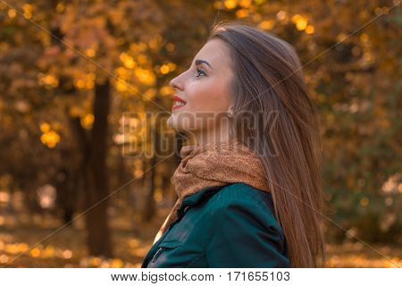 girl stands sideways in the Park and looks up close-up