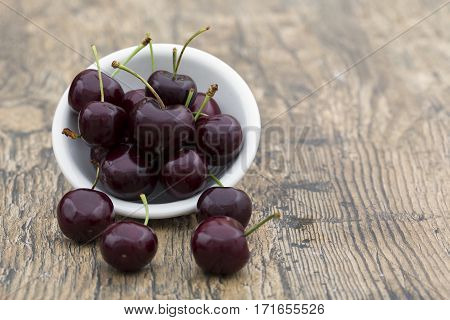 Close-up of cherries in a white bowl on brown wood background