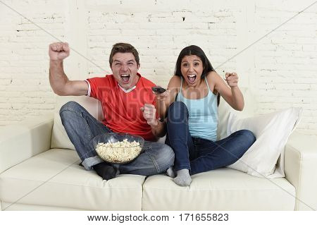 young couple watching tv sport football game excited celebrating together crazy happy goal raising arms in victory gesture jumping on home sofa couch screaming joyful