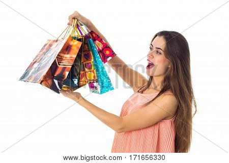 a young girl stands sideways and up large colored gift bags isolated on white