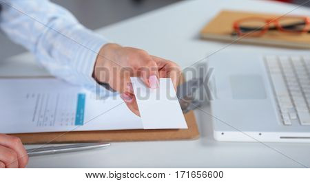 Business women sitting on desk and writing a paper.