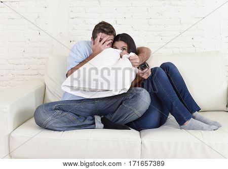 young happy attractive couple having fun at home enjoying watching television horror movie show or thriller film covering eyes with pillow together scared in shock at home couch terrified