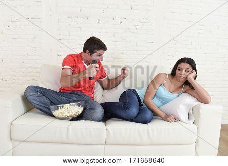 young couple watching tv sport football game with man excited celebrating crazy happy goal and wife or girlfriend bored and frustrated in relationship lifestyle concept