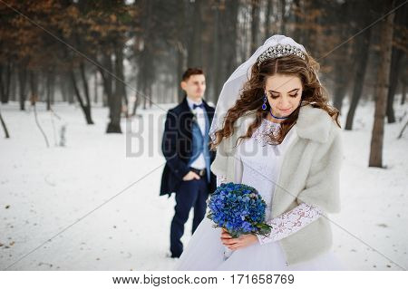 Young Stylish Wedding Couple At Forest On Winter Day. Loving Newlyweds On Snowy Weather. Bride On Fo