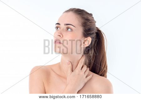 young nude girl looks away and keeps the ball neck is isolated on a white