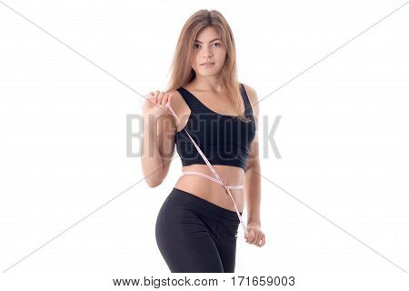 Pretty slim girl stands directly and measures the volume of a tape measure around her waist