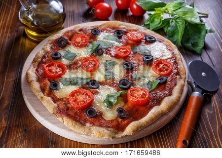 Healthy Whole Grain Pizza Margherita with Cherry Tomatoes, Mozzarella Cheese and Basil on a Cutting board