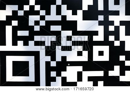 The black white and geometric pattern of a QR code.