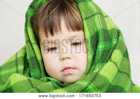 Child portrait in blanket warmingchildren care little girl wrapped in green warm blanketcomfortable winter concept