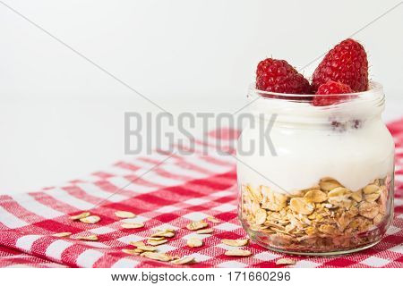 Overnight oatmeal with yogurt and raspberry on the checkered towel on the white background with copy space