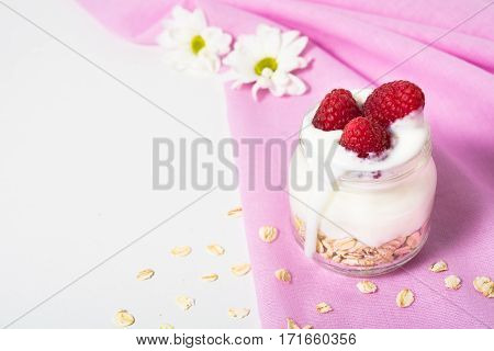 Overnight oatmeal with yogurt and raspberry on the pink material with flowers