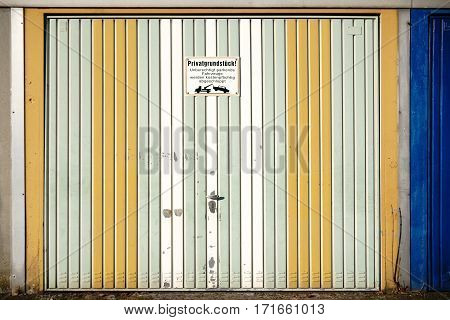 A striking garage door made of sheet metal strips and faded color.