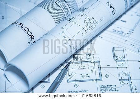 new construction drawing, pencil and rolls over a construction drawing of a house, interior diagram (drawing or design) with pen on blueprint