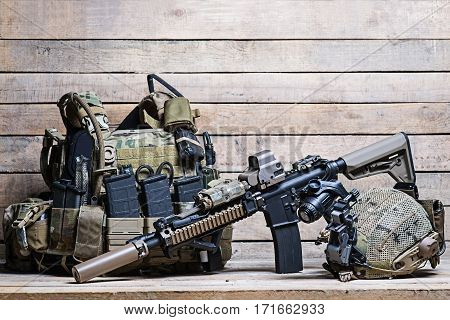 Military bulletproof vest,assult rifle,helmet with night-vision device on wooden background poster