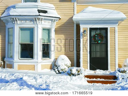 Snow piles up at the front door of an older home.