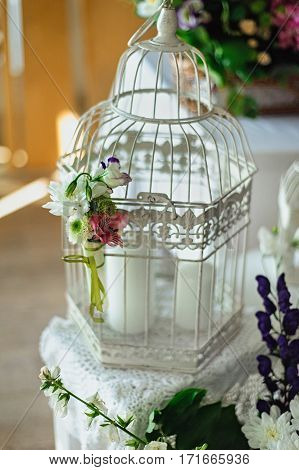 White Decorative Cage With Flowers And Leaves In Day Light