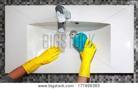 hands of woman in gloves who washes white sink in bathroom