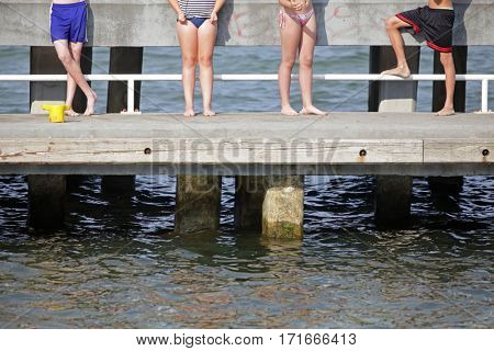 happiness - group of  faceless young people standing on pier and having sunbathe
